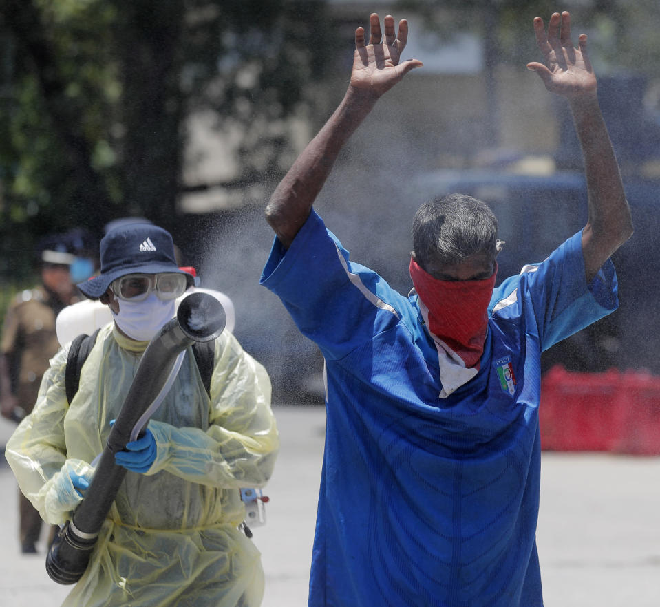 A Sri Lankan police officer sprays disinfectant on a homeless man before transporting him to an isolation center as a measure to prevent the spread of the new coronavirus during a lockdown in Colombo, Sri Lanka, Friday, April 17, 2020. Sri Lankan authorities claim they have largely managed to prevent community spreading through proper identification and isolation of people who came into contact with COVID-19 patients. (AP Photo/Eranga Jayawardena)