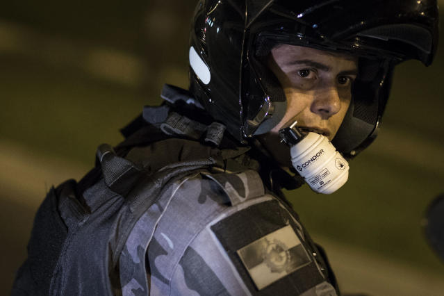 A riot police officer uses his front teeth to hold onto to a non-lethal grenade during an anti-government protest near the Cidade de Deus, or City of God slum, in Rio de Janeiro, Brazil, Friday, June 21, 2013. City centers around Brazil were still smoldering on Friday after 1 million protesters took to the streets amid growing calls on social media for a general strike next week. While most protesters were peaceful, some small groups clashed violently with police, who responded in some cases with tear gas, pepper spray and rubber bullets. (AP Photo/Felipe Dana)