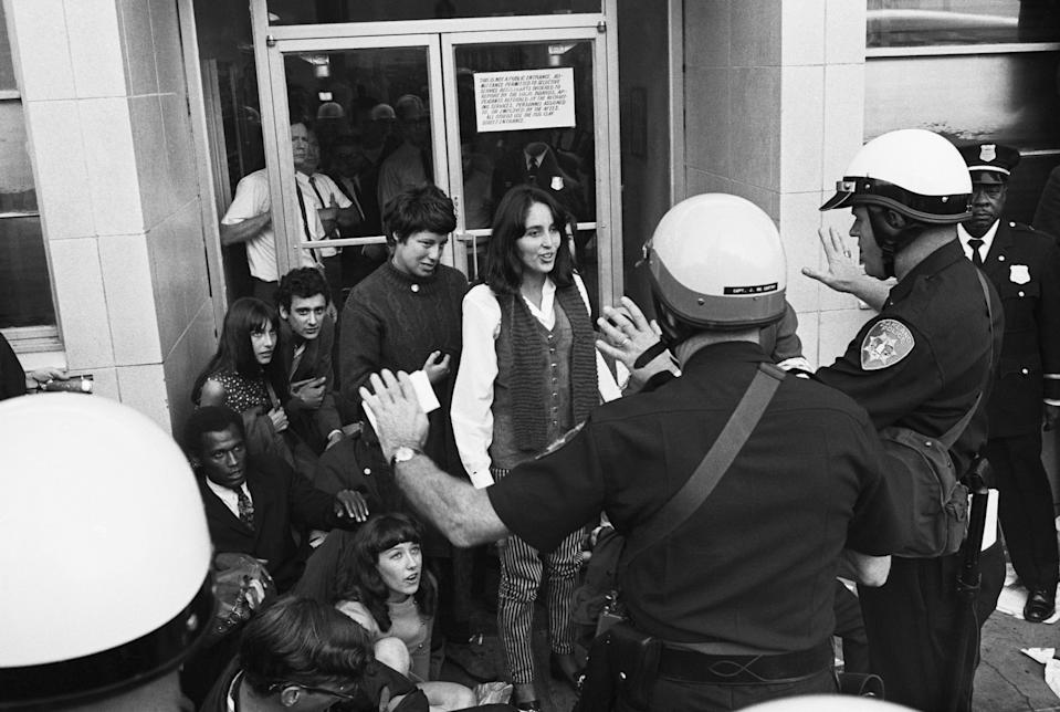 Singer Joan Baez (C) is stopped by police, as they advise her of her Constitutional rights, just prior to her arrest in front of the Oakland Induction Center on Oct. 16, 1967. Miss Baez and some 75 others were arrested as they attempted to block draftees from entering the center. More than 600 persons took place in the demonstration. (Bettmann Archive via Getty Images)