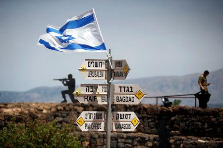FILE PHOTO: An Israeli soldier stands next to signs pointing out distances to different cities, on Mount Bental, an observation point in the Israeli-occupied Golan Heights that overlooks the Syrian side of the Quneitra crossing, Israel May 10, 2018. REUTERS/Ronen Zvulun/File photo