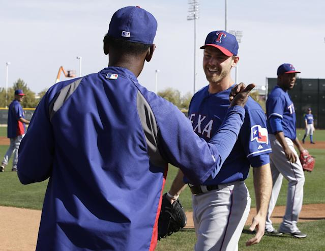 In this photo taken Feb. 23, 2014, Texas Rangers' manager Ron Washington, left, talks with Neal Cotts, right, as the two joke between fielding drills during spring training baseball practice in Surprise, Ariz. Cotts received an unexpected call from the Rangers, and last season made a record-setting comeback. (AP Photo/Tony Gutierrez)