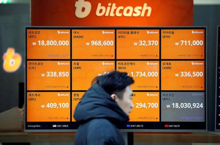 FILE PHOTO: A man walks past an electric board showing exchange rates of various cryptocurrencies including Bitcoin (top L) at a cryptocurrencies exchange in Seoul