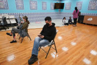 Mosque member Albert Capa's, foreground, wife and children are seen in the background as he sits in the observation area after being inoculated with the Johnson & Johnson COVID-19 vaccine at a pop up vaccinations site the Albanian Islamic Cultural Center, Thursday, April 8, 2021, in the Staten Island borough of New York. Ahead of Ramadan, Islamic leaders are using social media, virtual town halls and face-to-face discussions to spread the word that it's acceptable for Muslims to be vaccinated during daily fasting that happens during the holy month. (AP Photo/Mary Altaffer)