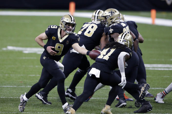 New Orleans Saints quarterback Drew Brees (9) hands off to running back Alvin Kamara (41) in the first half of an NFL wild-card playoff football game against the Chicago Bears in New Orleans, Sunday, Jan. 10, 2021. (AP Photo/Butch Dill)