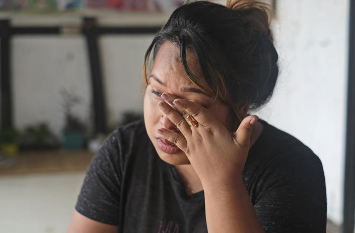 Diana Khumanthem, 30, wipes her tears as she recounts her COVID-19 experience sitting at home in Imphal, in the northeastern Indian state of Manipur, Monday, June 28, 2021. Diana lost both her mother and sister to the virus in May. Treatment costs wiped out the family's savings, and when the private hospital where she died wouldn't release her sister's body for last rites until a bill of about $5,000 was paid, she pawned the family's gold jewelry to moneylenders. When that wasn't enough, friends, relatives and her sister's colleagues helped. She still owes some $1,000. (AP Photo/Yirmiyan Arthur)