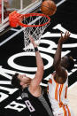 Atlanta Hawks' Clint Capela (15) shoots and scores against Sacramento Kings' Nemanja Bjelica (8) during the first half of an NBA basketball game on Saturday, March 13, 2021, in Atlanta. (AP Photo/Brynn Anderson)