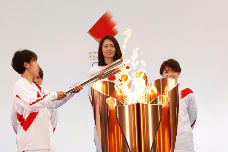 Japanese torchbearer Azusa Iwashimizu, a member of Japan women's national football team, lights the Olympic torch on day one of the torch relay in Naraha, Fukushima Prefecture