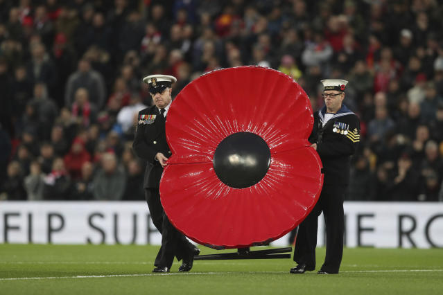 Soldiers hold a poppy for the Remembrance Day, during the English Premier League soccer match between Liverpool and Manchester City at Anfield stadium in Liverpool, England, Sunday, Nov. 10, 2019. (AP Photo/Jon Super)
