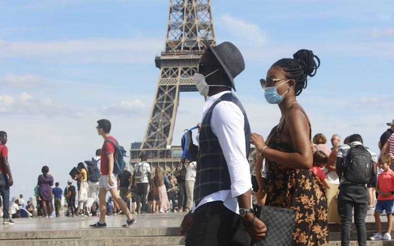 Tourists wear face masks as they walk close to the Eiffel Tower - Mehdi Taamallah/NurPhoto