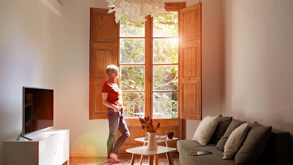 Shot of a mature woman standing by a window at home.