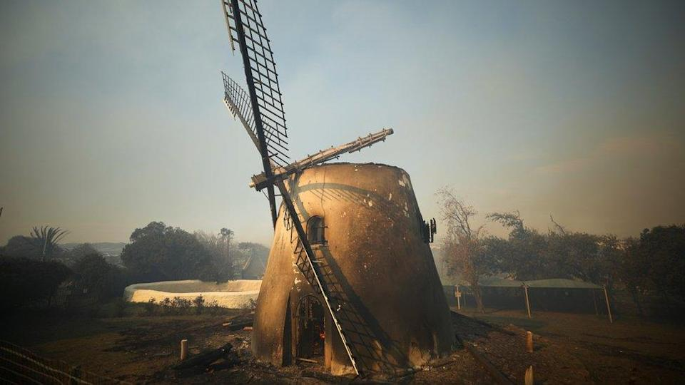 The historic Mostert's Mill smoulders as firefighters battle to contain a fire that broke out on the slopes of Table Mountain