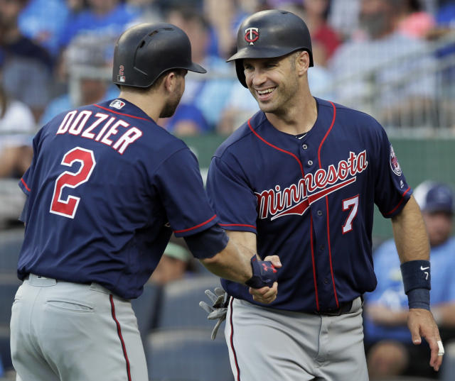 Minnesota Twins' Brian Dozier (2) congratulates teammate Joe Mauer (7) after Mauer scored on a single by Eddie Rosario during the first inning of a baseball game against the Kansas City Royals at Kauffman Stadium in Kansas City, Mo., Saturday, July 21, 2018. (AP Photo/Orlin Wagner)