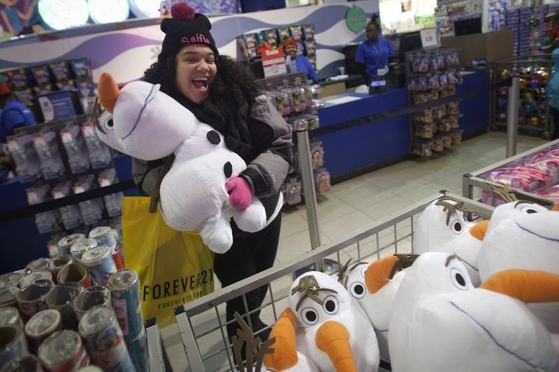 A girl poses with an Olaf plush toy from Disney's Frozen toy line at the Toys R Us store in Times Square in New York