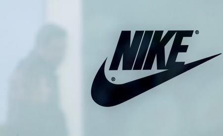 A customer is reflected in a shop window decorated with Nike store logo at the outlet village Belaya Dacha outside Moscow