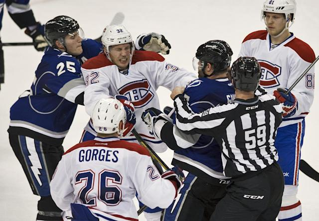 Linesman Steve Barton (59) breaks up a scuffle between Tampa Bay Lightning's Radko Gudas and Matthew Carle (25) with Montreal Canadiens' Travis Moen (32), Josh Gorges (26) and Lars Eller (81) during the second period of an NHL hockey game Saturday, Dec. 28, 2013, in Tampa, Fla. (AP Photo/Steve Nesius)