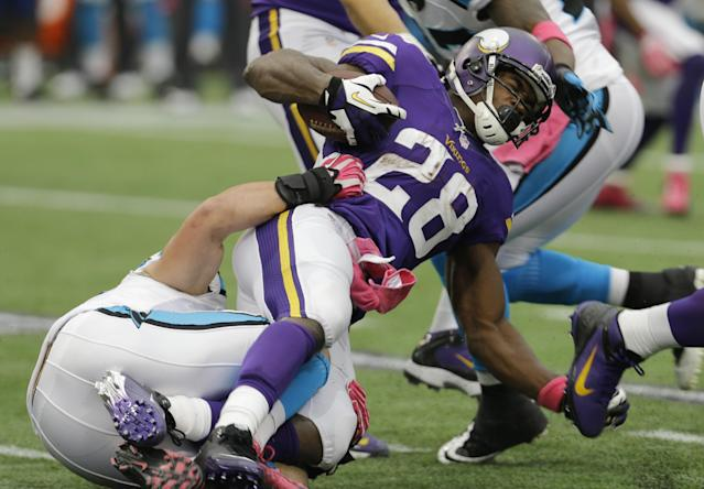 Minnesota Vikings running back Adrian Peterson, right, is tackled by Carolina Panthers middle linebacker Luke Kuechly during the first half of an NFL football game in Minneapolis, Sunday, Oct. 13, 2013. (AP Photo/Ann Heisenfelt)