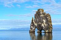 """Often referred to as the """"troll of northwest Iceland,"""" Hvítserkur rises 49 feet from from Húnaflói Bay like some sort of mythical beast. The rock—best viewed from Iceland's <a href=""""https://www.cntraveler.com/story/iceland-road-trip-arctic-coast-way?mbid=synd_yahoo_rss"""" rel=""""nofollow noopener"""" target=""""_blank"""" data-ylk=""""slk:Arctic Coast Way"""" class=""""link rapid-noclick-resp"""">Arctic Coast Way</a>—often looks like it's moving due to the birds that love to perch atop it, making the formation feel more like a living creature."""