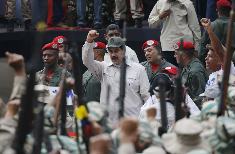 FILE - In this April 13, 2019 file photo, Venezuela's President Nicolas Maduro gestures to members of the Bolivarian Militia during their 10th anniversary celebration in Caracas, Venezuela. Last April, as a military uprising roiled Venezuela, Maduro's socialist government ordered pay TV providers to immediately cease transmission of CNN and the BBC. DirecTV, which is wholly owned by AT&T, quickly obliged, yanking the two networks off the air. (AP Photo/Ariana Cubillos, File)