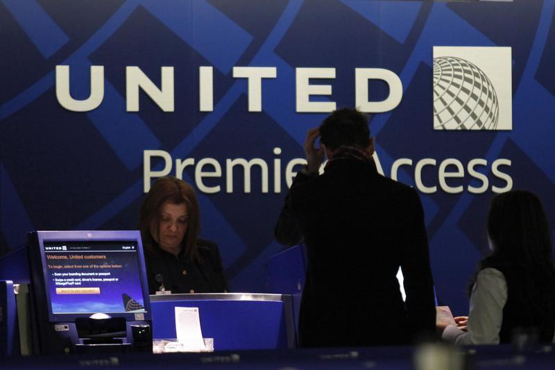 A worker from United attends to some customers during their check in process at Newark International airport in New Jersey