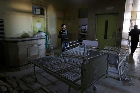 FILE PHOTO: People inspect damage in Omar Bin Abdulaziz hospital, in the rebel-held besieged area of Aleppo