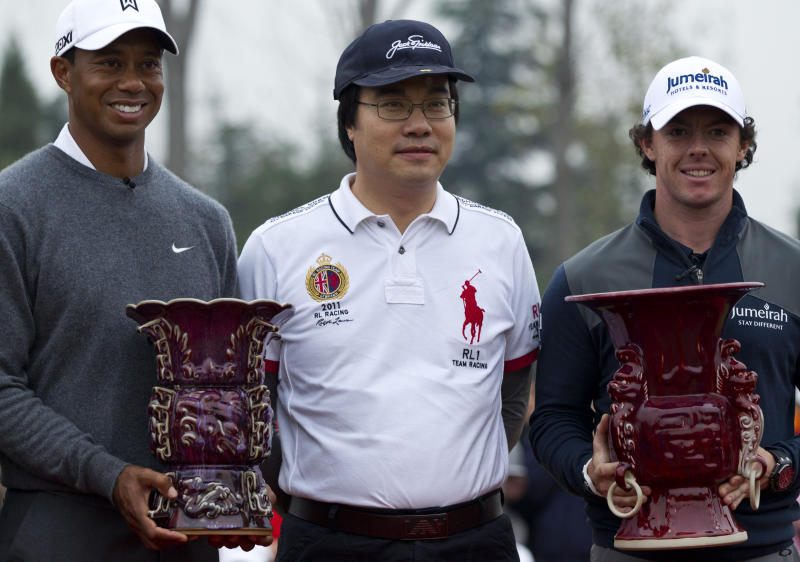 Tiger Woods of the United States, left, and Rory McIlroy of Northern Ireland, right, hold their trophies with Feng Changge, chairman of Harmony Group, after their 18-hole medal-match at the Lake Jinsha Golf Club in Zhengzhou, in central China's Henan province, Monday, Oct. 29, 2012. Rory McIlroy shot a 5-under 67 to beat Tiger Woods by one stroke in a head-to-head, 18-hole exhibition match between the world's two top-ranked golfers. (AP Photo/Alexander F. Yuan)