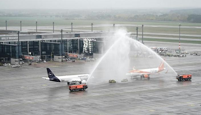 """Fire engines spray water to greet planes of airlines Lufthansa and EasyJet, the first flights to arrive at Berlin's """"Berlin Brandenburg Airport Willy Brandt"""""""
