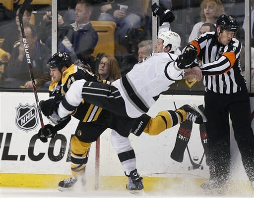 Los Angeles Kings center Colin Fraser (24) goes flying after colliding with Boston Bruins defenseman Andrew Ference (21) as referee Dave Jackson (8) protects himself in the second period of an NHL hockey game in Boston Tuesday, Dec. 13, 2011. (AP Photo/Elise Amendola)