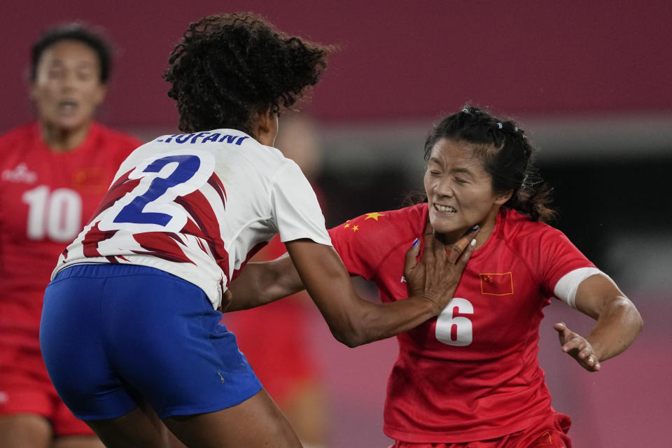 France's Anne-Cecile Ciofani, left, grapples with China's Wang Wanyu, in their women's rugby sevens quarterfinal match at the 2020 Summer Olympics, Friday, July 30, 2021 in Tokyo, Japan. (AP Photo/Shuji Kajiyama)
