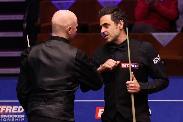 Ronnie O'Sullivan (right) bumps elbows with Anthony McGill