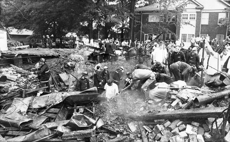 FILE - In this May 30, 1968 file photo, firefighters and volunteers dig through the wreckage of a daycare center after a bulldozer broke open a buried 1-inch pipeline that caused an explosion and fire in Hapeville, Ga. Nine people, including seven children, were killed in an explosion at the nursery when a bulldozer broke the pipeline, allowing gas to seep into the building before it ignited. Investigators said the tragedy could easily have been prevented: A simple device known as an excess flow valve, priced today at less than $20, could have cut off the escaping gas and saved those lives, federal investigators concluded. (AP Photo/File)