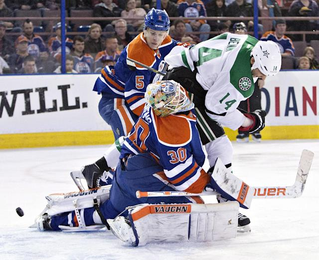 Dallas Stars' Jamie Benn (14) crashes into Edmonton Oilers goalie Ben Scrivens (30) as Mark Fayne (5) looks for the rebound during the first period of an NHL hockey game in Edmonton, Alberta, on Sunday, Dec. 21, 2014. (AP Photo/The Canadian Press, Jason Franson)