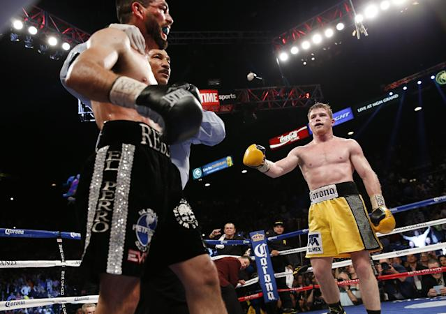 Alfredo Angulo of Mexicali Mexico, left, reacts to referee Tony Weeks stopping of the fight in the 10th round against Saul Alvarez of Guadalajara Mexico during their super welterweight boxing match, Saturday, March 8, 2014, at The MGM Grand Garden Arena in Las Vegas. Alvarez won by TKO. (AP Photo/Eric Jamison)