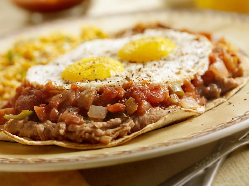 "<p>Refried beans don't just boost the protein content of eggs, they also add a ton of flavor. And if you happen to have some salsa lying around, you've basically got yourself some <a href=""https://www.thedailymeal.com/recipes/huevos-rancheros-recipe-0?referrer=yahoo&category=beauty_food&include_utm=1&utm_medium=referral&utm_source=yahoo&utm_campaign=feed"" rel=""nofollow noopener"" target=""_blank"" data-ylk=""slk:huevos rancheros"" class=""link rapid-noclick-resp"">huevos rancheros</a>.</p>"
