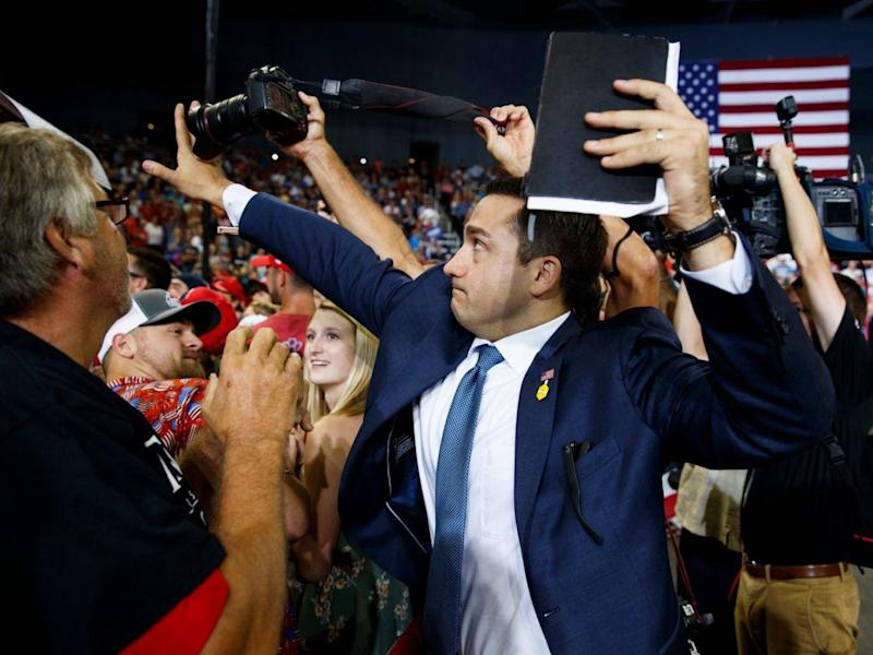 A volunteer member of the advance team for president Donald Trump blocks a camera as a photojournalist attempts to take a photo of a protester during a campaign rally (AP)