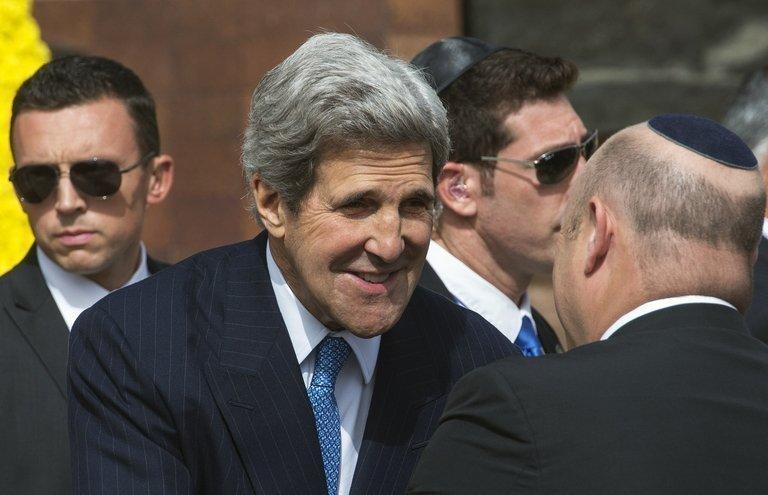 """US Secretary of State John Kerry (C) greets officials shortly before placing a wreath from the United States at the Yad Vashem memorial in Jerusalem during Holocaust Memorial Day on April 8, 2013. Kerry on Monday said he was pursuing a """"quiet strategy"""" for breaking the years-long impasse in Israeli-Palestinian peace talks, warning the process could not be rushed"""