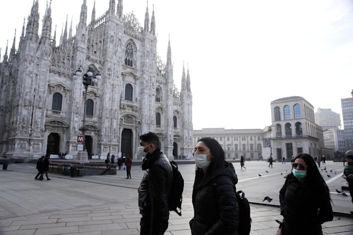 People walk past the Duomo in Milan on February 23.