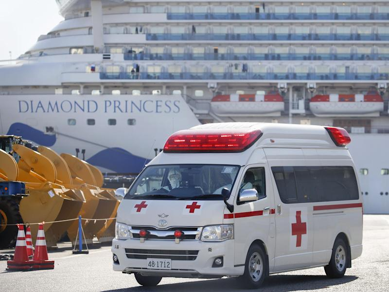 An ambulance leaves Daikoku Pier in Yokohama on Feb. 17, 2020, with the Diamond Princess cruise ship seen in the background. The ship has been kept in quarantine amid the spread of a new coronavirus among people on board.