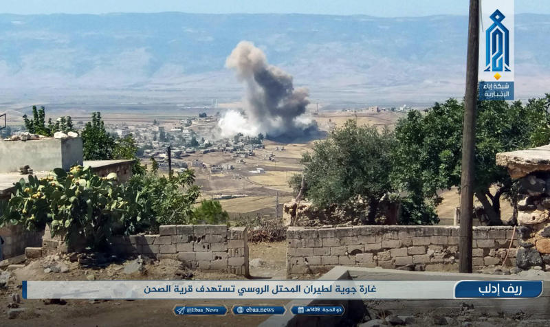 """This photo released Tuesday, Sept 4, 2018 by the al-Qaida-affiliated Ibaa News Agency, shows smoke rising over buildings that were hit by airstrikes, in al-Sahan village, in the northern province of Idlib, Syria. Arabic reads, """"Air raid by the Russian occupation plane targets al-Sahan village."""" Despite dire U.S. warnings and fears of a humanitarian disaster, the Trump administration has little leverage to stop Russia, Iran and Syria pressing ahead with a massive military assault against Syria's northwest Idlib province. (Ibaa News Agency, via AP)"""
