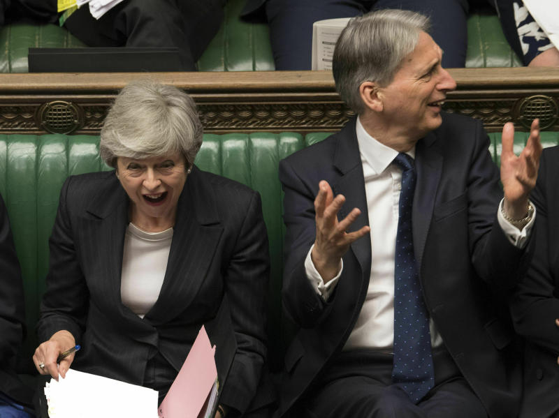 In this image made available by UK Parliament, Britain's Prime Minister Theresa May, left, and Chancellor Philip Hammond react during Prime Minister's Questions in the House of Commons, London, Wednesday, May 22, 2019. British Prime Minister Theresa May dug in Wednesday against a growing push by both rivals and former allies to remove her from office as her attempts to lead Britain out of the European Union appeared to be headed for a dead end. (Mark Duffy/UK Parliament via AP)