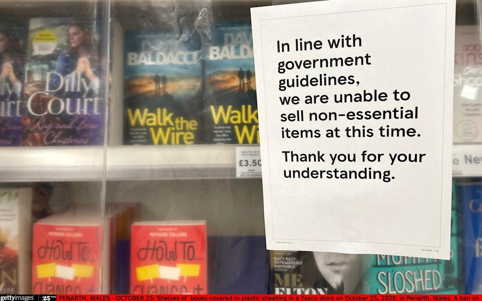 Shelves of books covered in plastic sheeting in a Tesco in Penarth, Wales - Getty Images
