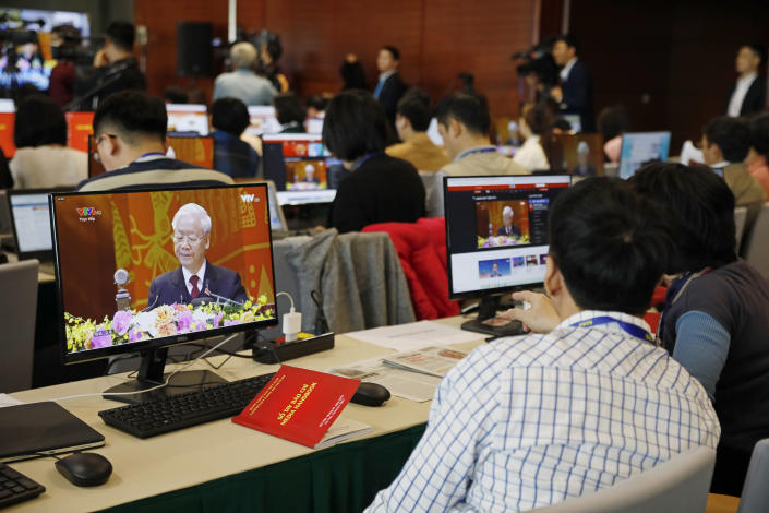 Journalists, sitting at the media center, watch Nguyen Phu Trong, General Secretary of the Communist Party of Vietnam delivering a speech, on screens, during the opening ceremony of the 13th National Congress of Vietnam's Communist Party (VCP), in Hanoi, Vietnam on Tuesday, Jan. 26, 2021. Vietnam's ruling Communist Party has begun a crucial weeklong meeting in the capital Hanoi to set the nation's path for the next five years and appoint the country's top leaders. (AP Photo/Minh Hoang)