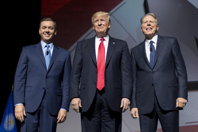 President Donald Trump (center) stands beside NRA CEO and executive vice president Wayne LaPierre (right)andNRA-ILA executive director Chris Cox (left). The NRA donated over $30 million to Trump's presidential campaign in 2016. (JIM WATSON via Getty Images)