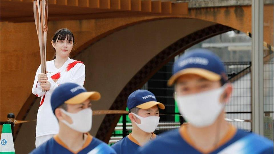 """A torch bearer holds the Olympic torch at Futaba station, inside one of the difficult-to-return zones set since Fukushima""""s 2011 nuclear disaster, on the first day of the Tokyo 2020 Olympic torch relay, in Futaba, Fukushima Prefecture, Japan March 25, 2021."""