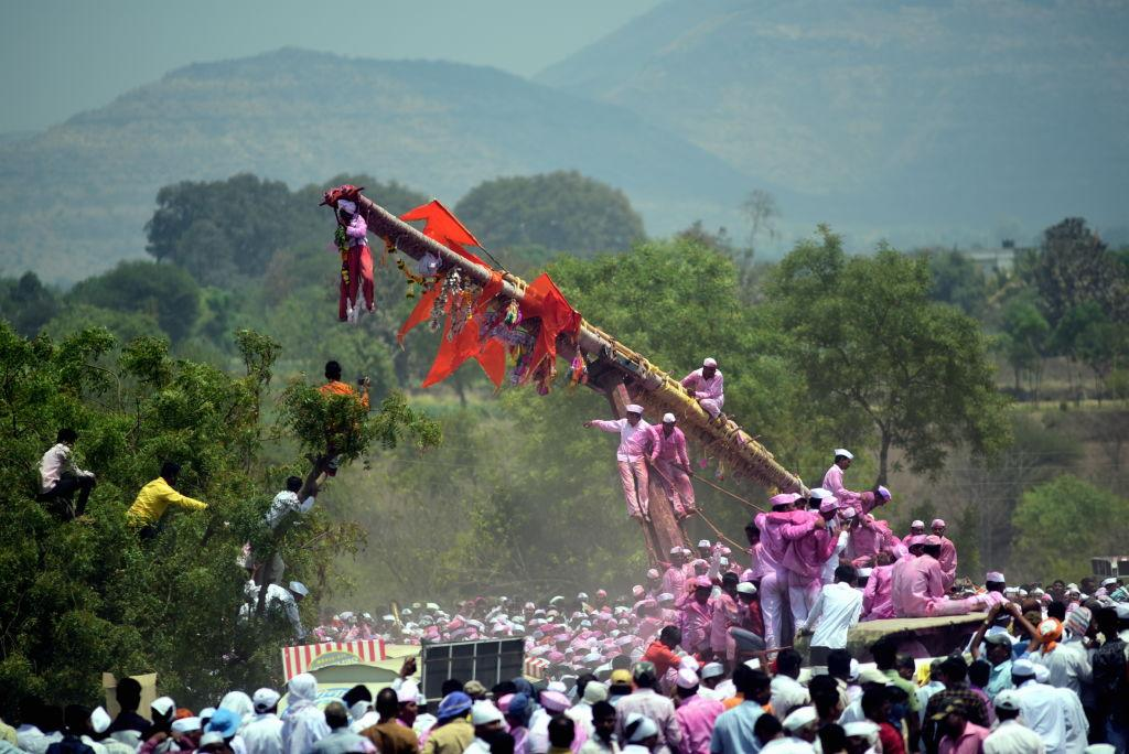 <p>The devotee whose wish was granted hangs from the Bagad on March 25, 2019 in Satara, India. The Bagad, a 40-feet see-saw made of bamboo is pulled by atleast 4 bullock carts at a time. Over 250-300 bullocks are brought during the occasion – The Bagad Rath Yatra at Bavdhan in Satara district sees pilgrims from all over the state, who come together to worship Lord Bhairavnath. (Photo from Vijayanand Gupta/Hindustan Times via Getty Images) </p>