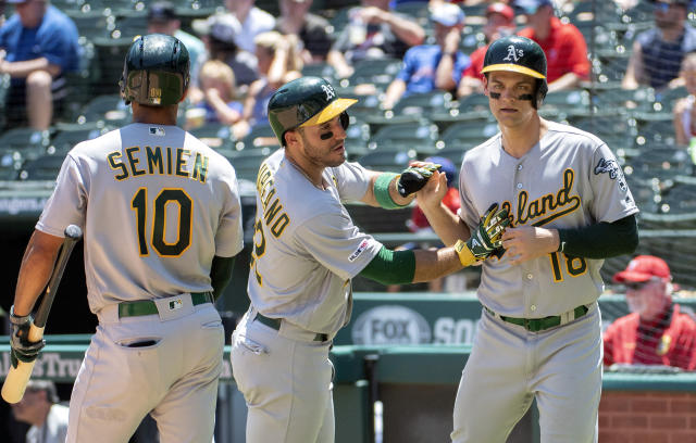 Oakland Athletics' Ramon Laureano, center, and Chad Pinder, right, celebrate after scoring on a pinch hit double by Josh Phegley as Marcus Semien (10) looks on during the fourth inning of the first baseball game of a doubleheader against the Texas Rangers, Saturday, June 8, 2019, in Arlington, Texas. (AP Photo/Jeffrey McWhorter)