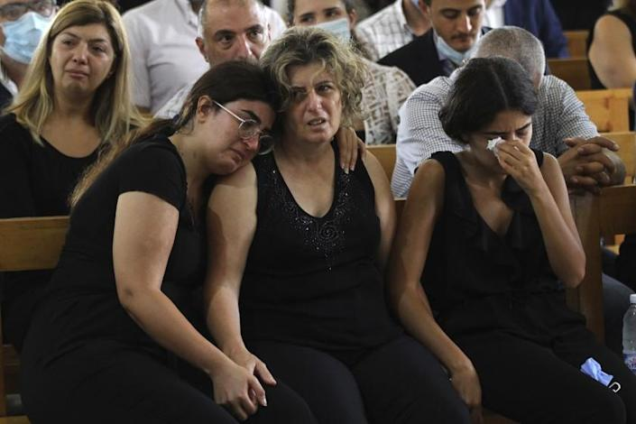 """The sisters of Nicole Helou flank their mother as they mourn in Sarba, Lebanon, on Aug. 6, 2020. Helou was among those killed in the blast two days earlier in Beirut. <span class=""""copyright"""">(Mohammed Zaatari / Associated Press)</span>"""