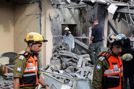 Israeli policemen and soldiers inspect a damaged house that was hit by a rocket north of Tel Aviv Israel