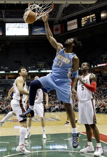 Denver Nuggets' Nene (31) dunks over Milwaukee Bucks' Stephen Jackson (5) and Carlos Delfino, left, during the first half of an NBA basketball game, Tuesday, Jan. 17, 2012, in Milwaukee. (AP Photo/Morry Gash)