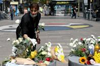 A woman leaves flowers on Barcelona's Las Ramblas boulevard, where one of the attackers rammed a van into pedestrians
