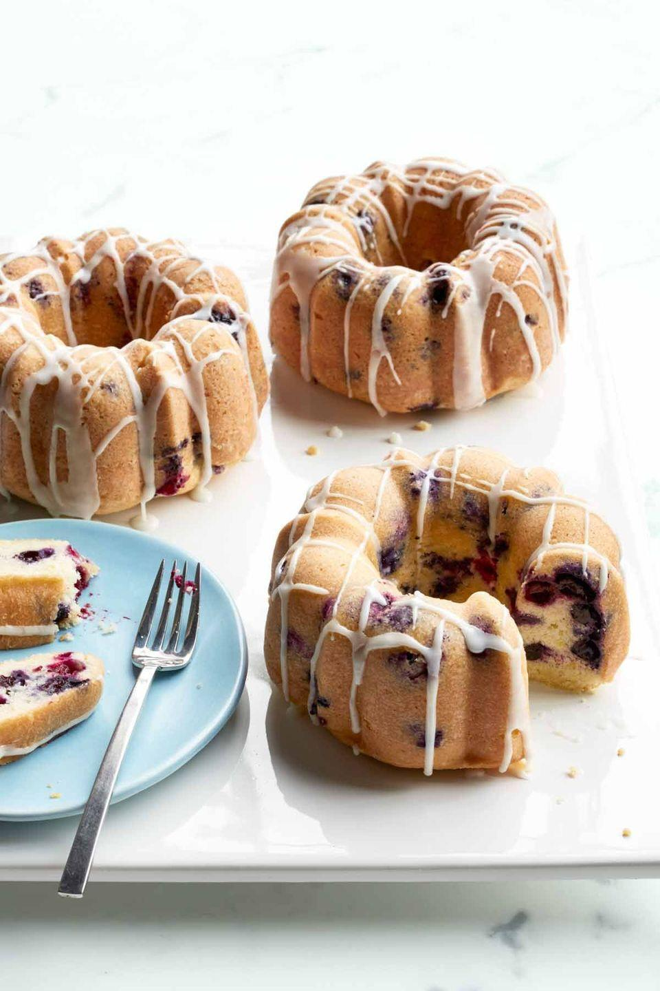 """<p>With this recipe, you can either make four tiny bundt cakes or a full-sized one for the whole family to enjoy.</p><p><em><strong><a href=""""https://www.womansday.com/food-recipes/food-drinks/recipes/a50261/mini-lemon-blueberry-bundt-cakes-recipe-wdy0515/"""" rel=""""nofollow noopener"""" target=""""_blank"""" data-ylk=""""slk:Get the Mini Lemon Berry Bundt Cakes recipe."""" class=""""link rapid-noclick-resp"""">Get the Mini Lemon Berry Bundt Cakes recipe.</a></strong></em></p>"""